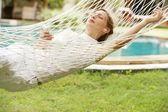 Young woman laying and relaxing on a white hammock — Stock Photo