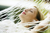 Attractive blonde woman laying down on a hammock — Stok fotoğraf