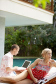 Sophisticated couple relaxing by the swimming pool of their holiday home garden — Stock Photo