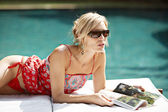 Sophisticated woman lounging by a swimming pool and reading a magazine. — Stock Photo