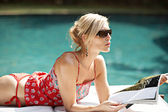 Fashionable attractive woman lounging by a swimming pool — Stock Photo