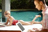 Casal jovem sofisticado relaxante junto à piscina — Foto Stock