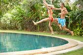Diversión joven pareja saltando a una piscina tropical — Foto de Stock