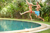 Young fun couple jumping into a tropical swimming pool — Foto Stock