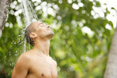 Young attractive man having a shower in a tropical garden — Stock Photo