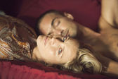 Portrait of a young couple laying down on a sofa. — Stockfoto