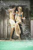 Water being splashed onto a young couple in swimwear by a swimming pool. — Stock Photo