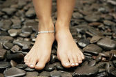 Woman's feet wearing an anklelet and standing on black stones. — Stock Photo