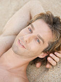 Attractive man sunbathing on a beach. — Stock Photo