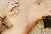Body part detail of a man sunbathing on a golden sand beach — Stock Photo