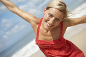 Attractive blonde woman on a beach with arms outstretched — Stock Photo
