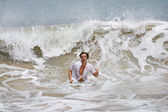 Attractive young man running out of the wild ocean, with a large wave behing him. — Stock Photo