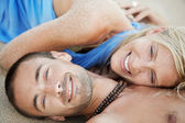 Young attractive couple laying down on golden sand — Foto Stock