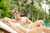 Young couple relaxing on a sun bed in a villa's tropical garden while on vacation. — Stock Photo