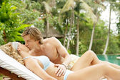Young couple relaxing on a sun bed and kissing — Stock Photo
