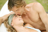 Portrait of a young couple relaxing on a sun bed and kissing — Stock Photo