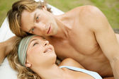 Portrait of a young couple relaxing on a sun bed — Stock Photo