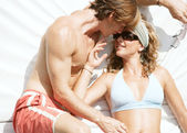 Young couple relaxing and being affectionate on a sunbed while on vacation. — Stock Photo