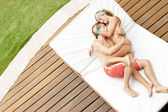 Attractive couple kissing and hugging in a modern home's garden. — Stock Photo