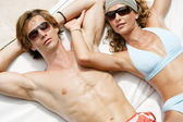 Attractive couple sunbathing and wearing sunglasses while sharing a sun bed. — Stockfoto