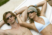 Young attractive couple sunbathing and wearing sunglasses. — Стоковое фото