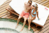 Attractive couple sunbathing and sharing a sun bed by a swimming pool. — Stock Photo