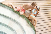 Attractive couple sunbathing and being affectionate while sitting by a swimming pool's steps — Stock Photo