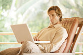 Young man using a laptop computer — Stock Photo