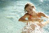 Mujer joven sonriendo en una piscina — Foto de Stock