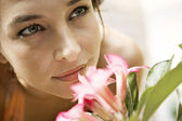 Beautiful young woman smelling a pink flower — Stockfoto