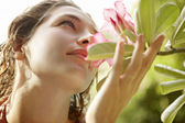 Beautiful young woman holding a flower close to her nose — Stock Photo