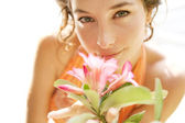 Young attractive girl smelling a tropical pink flower — Stock Photo