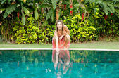 Woman crouching by swimming pool and touching the water. — Stock Photo