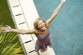 Attractive young woman smiling under the rain with arms outstretched — Stock Photo