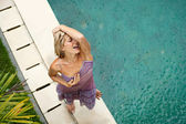 Woman by a swimming pool under falling rain in the summer — Stock Photo