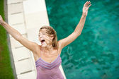 Woman enjoying the rain while standing outdoors by a swimming pool. — Stock Photo