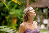 Attractive woman under tropical rain in an exotic garden. — Stock Photo