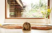 Vista trasera de una mujer joven que se inclina hacia atrás, mientras que en el baño de un centro de rehabilitación. — Foto de Stock
