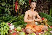 Jonge man in een yoga-positie in een exotische tuin. — Stockfoto