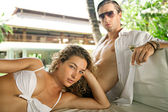 Exy young couple lounging on an outdoors tropical bed — Stock Photo