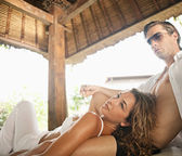 Sexy young couple lounging on an outdoors tropical bed — Stock Photo