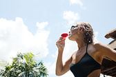 Attractive woman drinking a red cocktail glass while standing against a holiday hotel building — Stock Photo