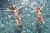 Over head view of two young women wearing bikinis and floating in water while holding hands, full frame. — Stock Photo