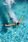Homme plonger dans une piscine, formant une forme de flèche et laisser une trace derrière lui. — Photo