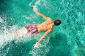 Over head rear view of a young man swimming under water in a blue swimming pool while on vacation. — Stock Photo