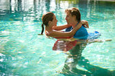 Sexy young couple submerged in a swimming pool while dressed, hugging and kissing while on a tropical destination vacation. — Stock Photo