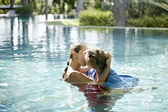 Couple submerged into a swimming pool, kissing and hugging while dressed. — Stock Photo