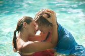 Sexy young couple submerged in a swimming pool while dressed — Stock Photo