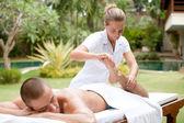 Joven masajista masaje y estirando el cuerpo de un hombre atractivo en un jardín tropical hotel — Foto de Stock