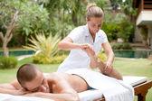 Young masseuse massaging and stretching the body of an attractive man in a tropical hotel garden — Stock Photo